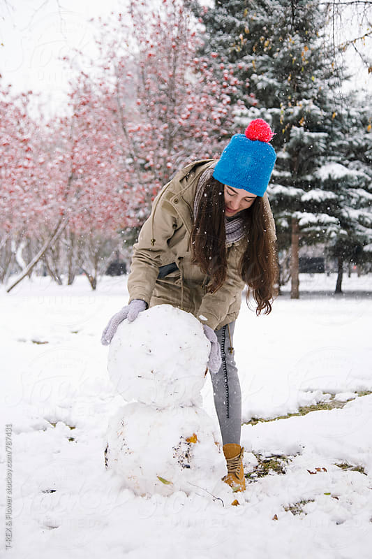 Young woman making snowman by T-REX & Flower for Stocksy United