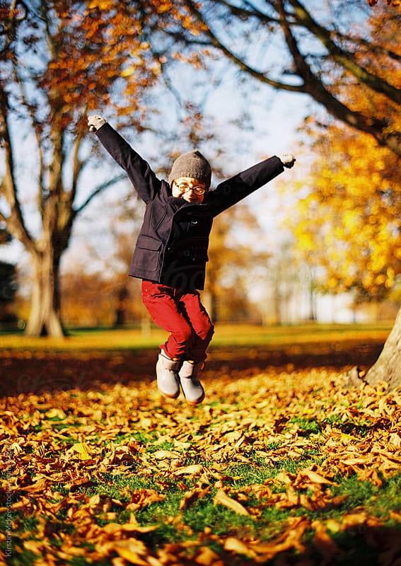 Boy jumping in the autumnal leaves.  by Kirstin Mckee for Stocksy United