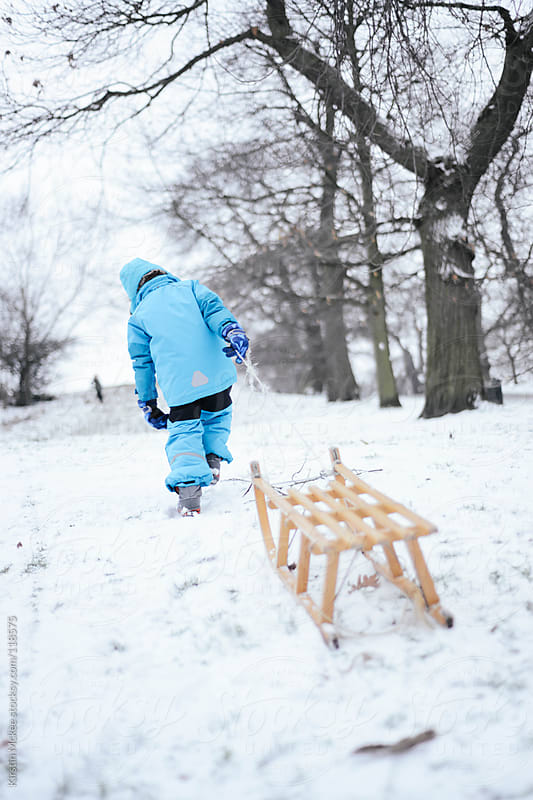 Boy pulling a wooden sledge up a hill by Kirstin Mckee for Stocksy United