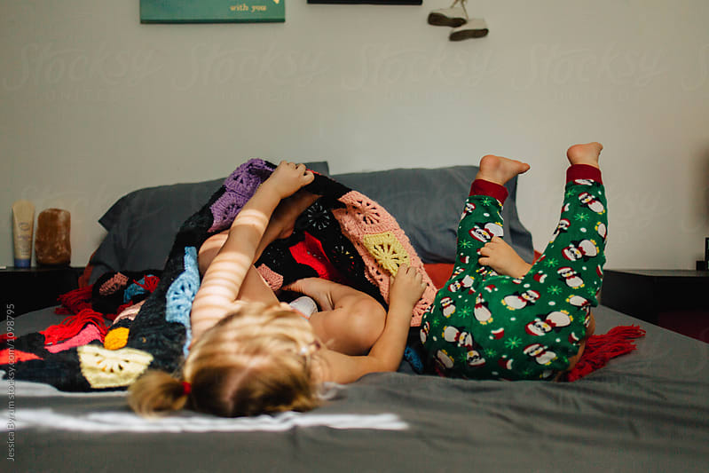 Happy toddler siblings playing and snuggling on a bed with a colorful blanket. by Jessica Byrum for Stocksy United