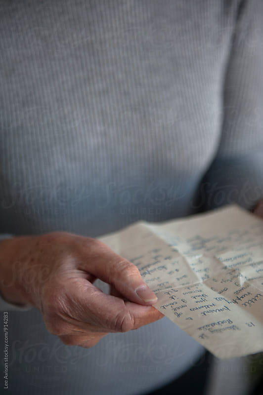 senior woman holding a hand written letter  by Lee Avison for Stocksy United