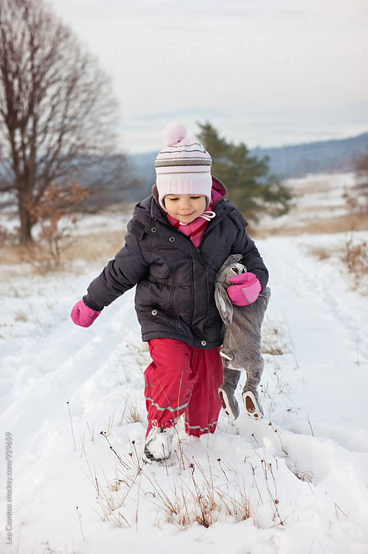 Toddler walking on a snow covered path holding her toy bunny by Lea Csontos for Stocksy United