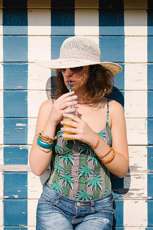 Stylish woman with hat drinking juice on the beach by Brkati Krokodil for Stocksy United