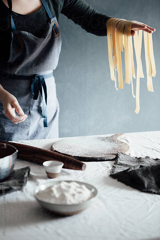Woman making homemade pasta by Ellie Baygulov for Stocksy United