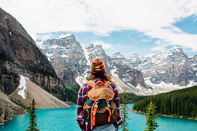 A woman wearing a backpack looking out towards a blue lake by Kristen Curette Hines for Stocksy United