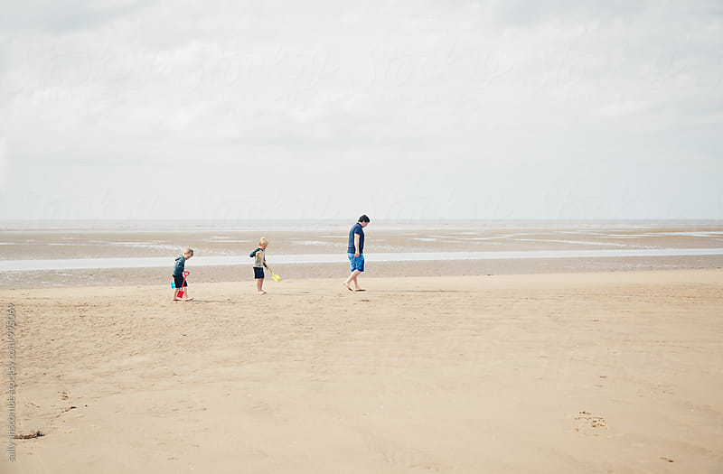 Father and two sons walking on the beach together by sally anscombe for Stocksy United