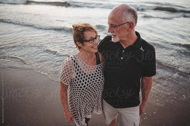 Content middle aged, retired couple together outside hanging out on ocean beach by Rob and Julia Campbell for Stocksy United