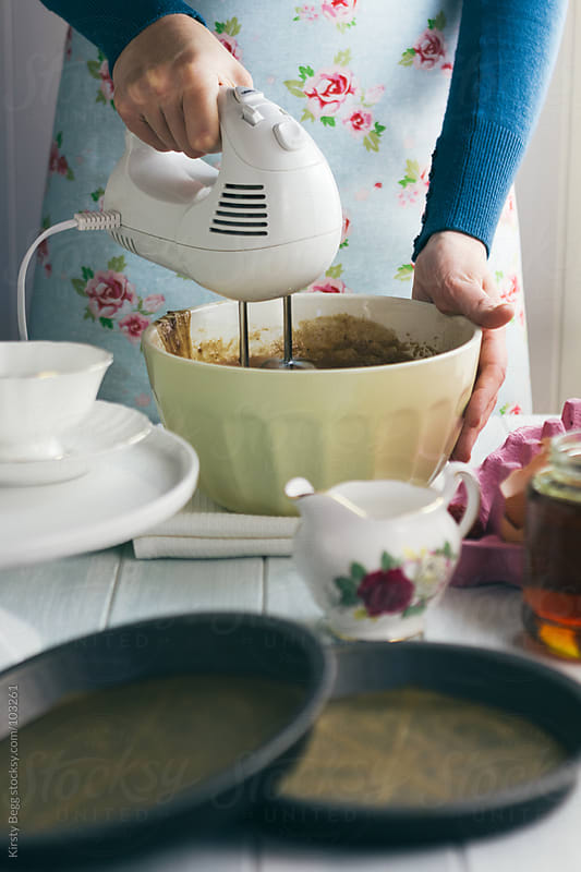 Woman whisking ingredients to make chocolate cake by Kirsty Begg for Stocksy United