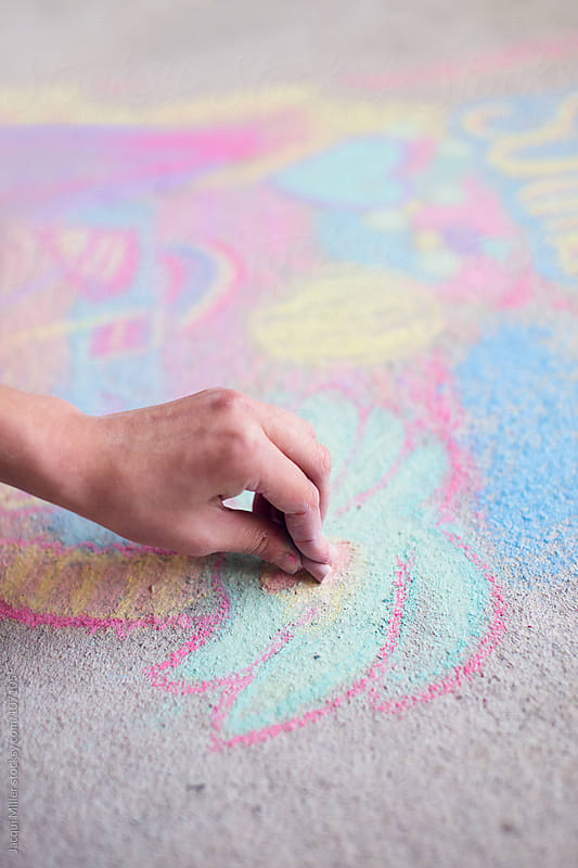 Girl draws with chalk on a concrete floor by Jacqui Miller for Stocksy United