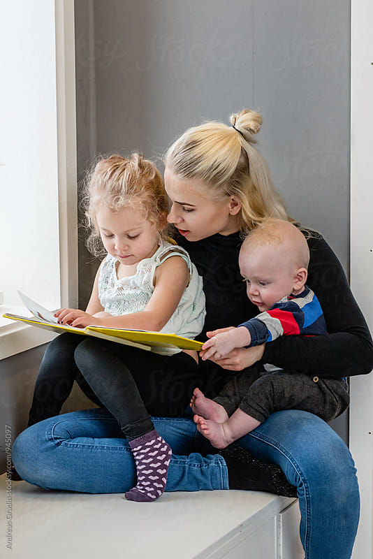 family reading a book by Andreas Gradin for Stocksy United