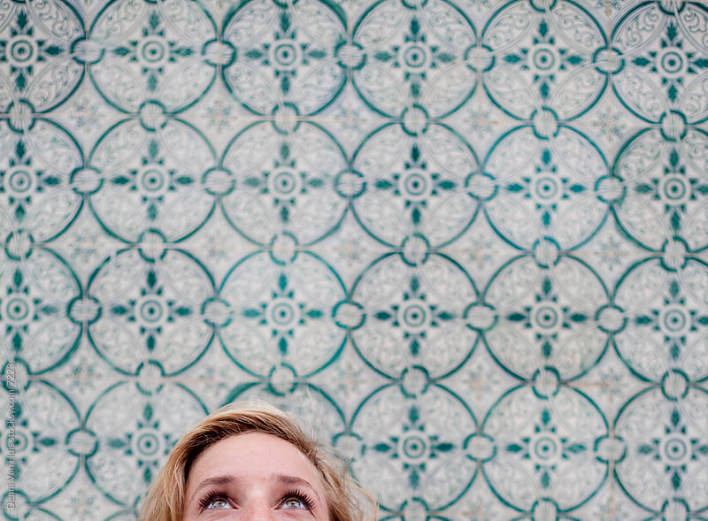 Young beautiful women looks up with clear bright eyes in front of a tiled wall by Denni Van Huis for Stocksy United