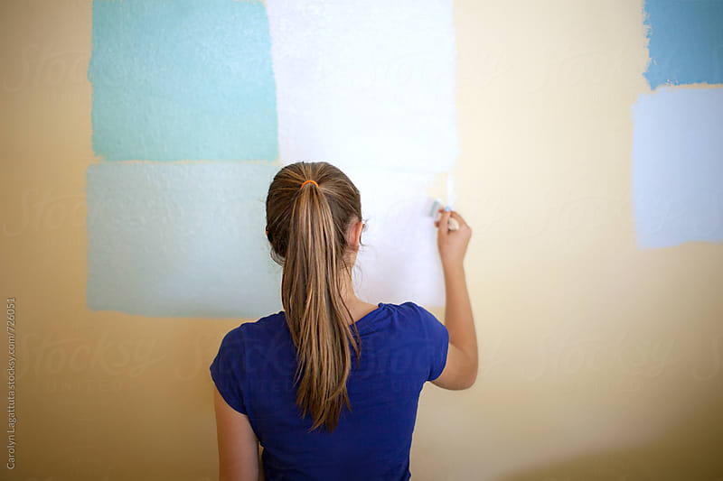 Teenage girl putting paint swatches on  the wall in her bedroom by Carolyn Lagattuta for Stocksy United
