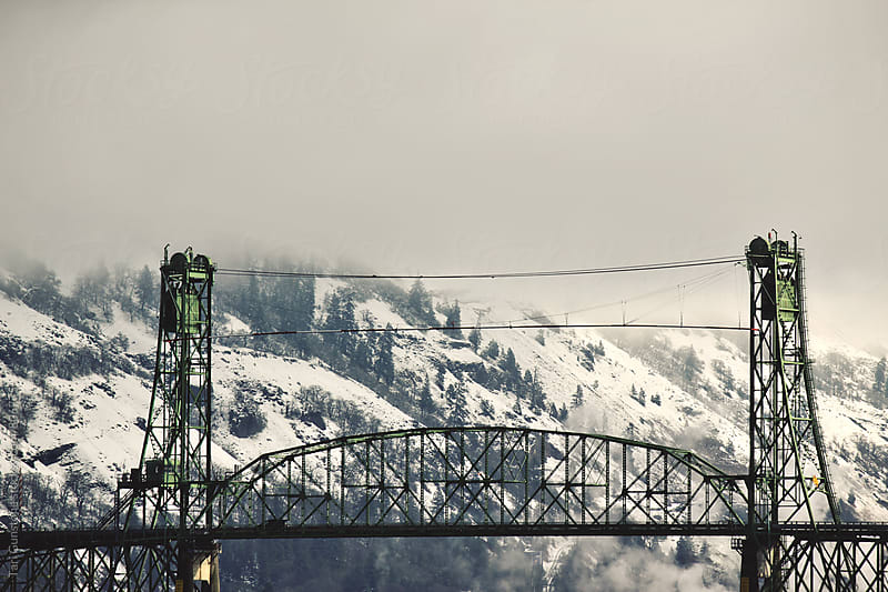 Bridge with snow covered hills in background by Tari Gunstone for Stocksy United