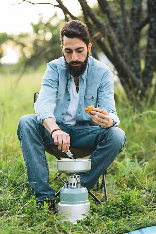 Young bearded man preparing food by Aleksandar Novoselski for Stocksy United