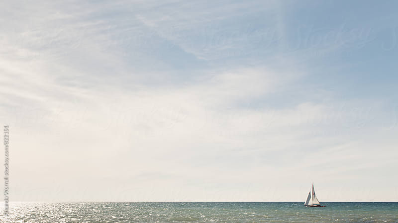 A sailboat sailing towards the sun on Lake Michigan by Amanda Worrall for Stocksy United