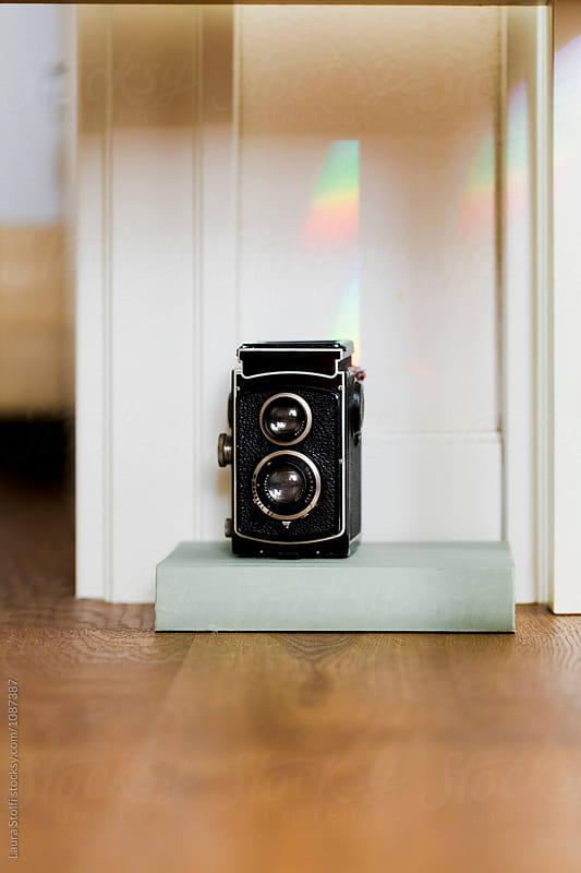 Twin lens reflex and rainbow on book by Laura Stolfi for Stocksy United