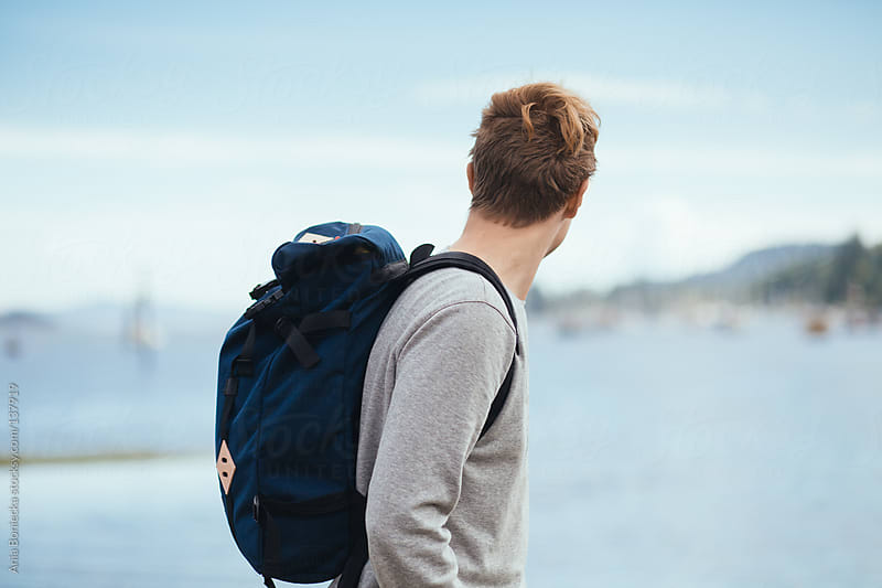 A blonde man looking out into a harbour wearing a backpack by Ania Boniecka for Stocksy United