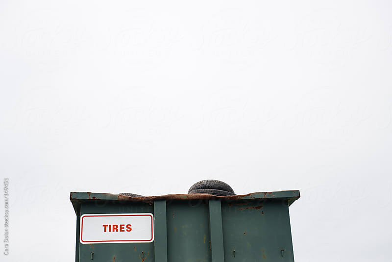 Dumpster filled with tires at a recycling center by Cara Dolan for Stocksy United