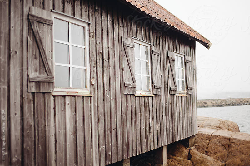 Grey fisheman hut by the sea by Jonas Räfling for Stocksy United