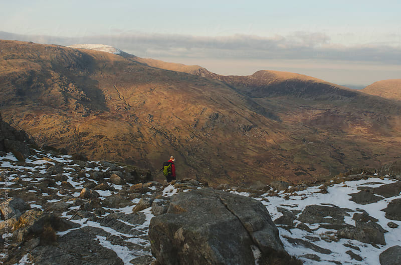 Lone Hiker at the Edge of a Mountain by Neil Warburton for Stocksy United