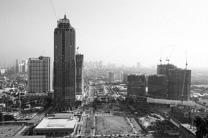 Construction of high-rise office buildings in full swing in a commercial district in the Philippines by Lawrence del Mundo for Stocksy United