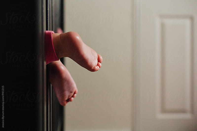 Toddler feet hanging out of crib by Jessica Byrum for Stocksy United