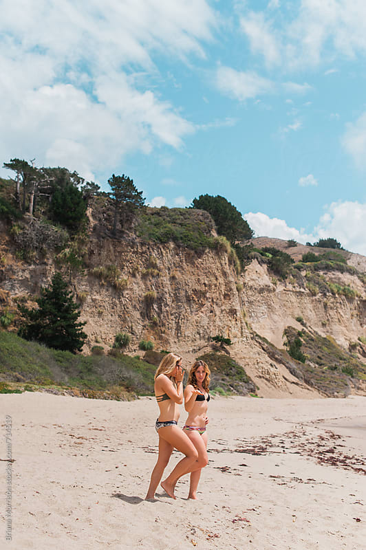 Two Women in Bikinis Walking on a Beach by Briana Morrison for Stocksy United