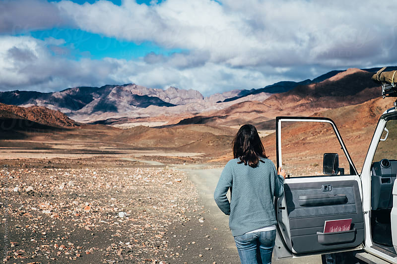 woman on a road trip standing outside her car looking at a rugged mountain landscape by Micky Wiswedel for Stocksy United