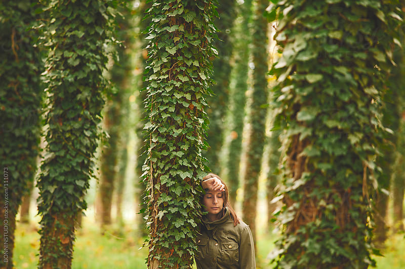 Young woman supported on a tree. Autumnal forest. by BONNINSTUDIO for Stocksy United