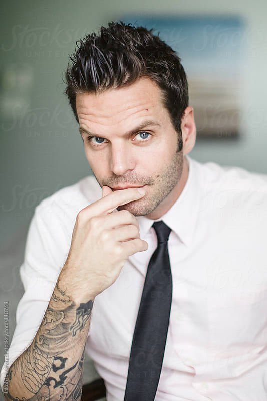 Handsome man with tattoos in a white shirt and black tie by Jakob for Stocksy United