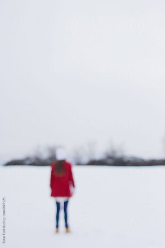 blurry young woman in red coat stands alone in snowy field by Tana Teel for Stocksy United
