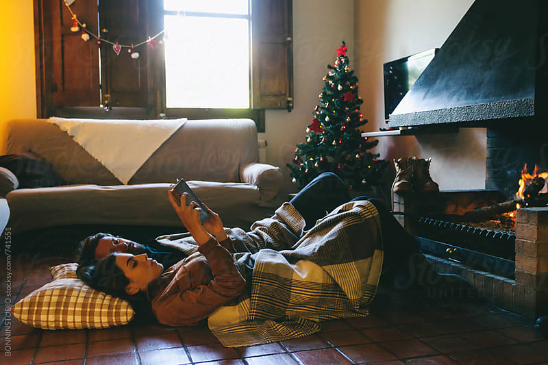 Young couple reading a book resting by the fireplace. by BONNINSTUDIO for Stocksy United