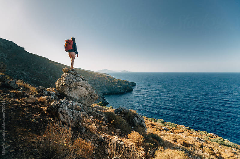 female hiker on a rocky outcrop overlooking a sea view in Kalymnos, Greece by Micky Wiswedel for Stocksy United