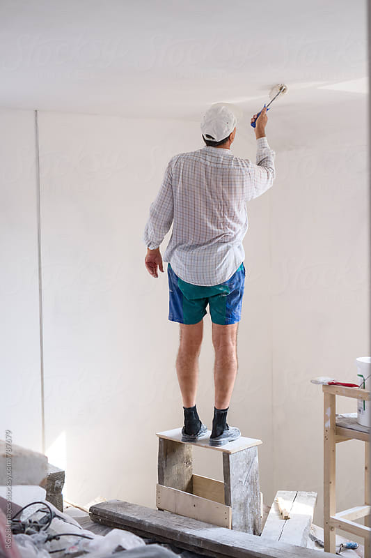 Man standing on a scaffold painting the home interior  by RG&B Images for Stocksy United
