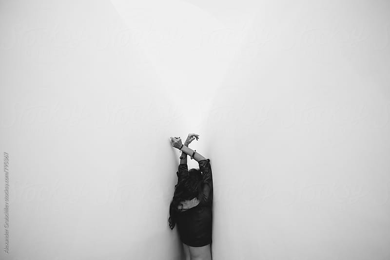 Woman By White Wall by Alexander Grabchilev for Stocksy United