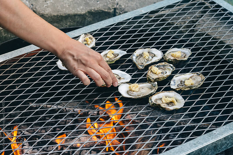 Placing oysters over the open fire by Jen Grantham for Stocksy United