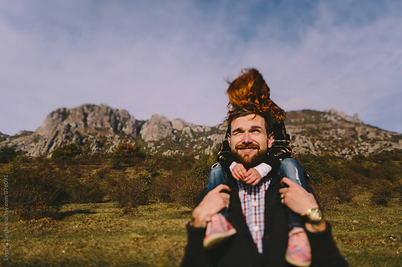 Father carries daugther on his shoulders by Evgenij Yulkin for Stocksy United