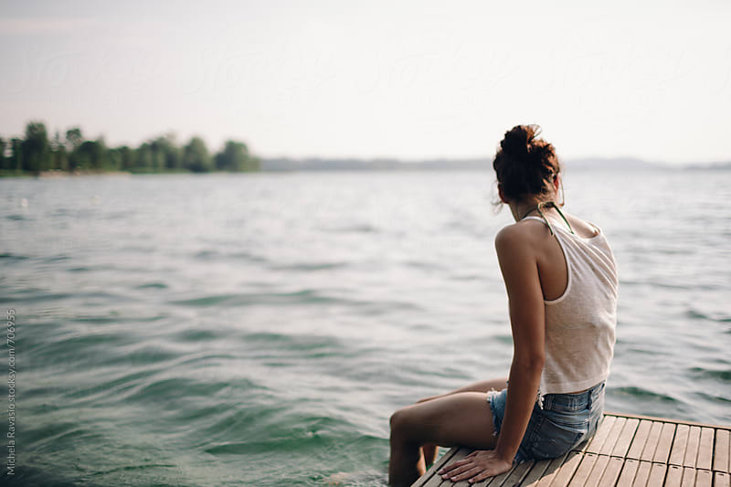 Girl sitting on a pier with her feet in the water by michela ravasio for Stocksy United