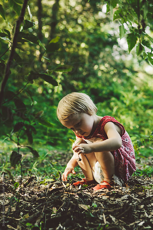 Little Girl Outside Holding an Uprooted Plant by Stephen Morris for Stocksy United