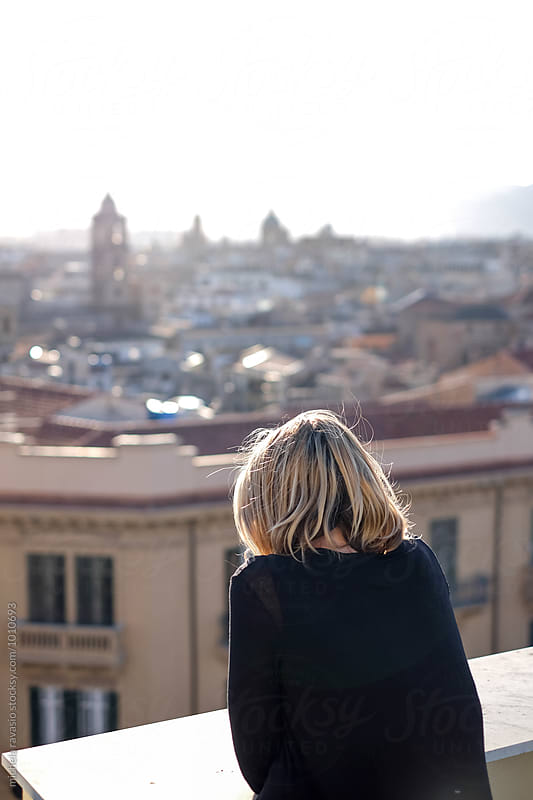 Blonde woman looking at Palermo from the terrace of tall building by michela ravasio for Stocksy United