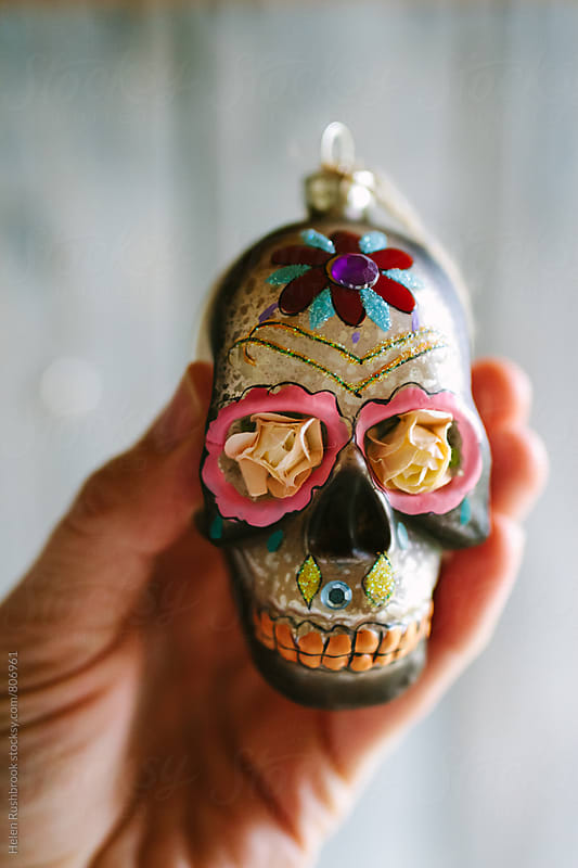 Hand holding a Day of The Dead Christmas decoration. by Helen Rushbrook for Stocksy United