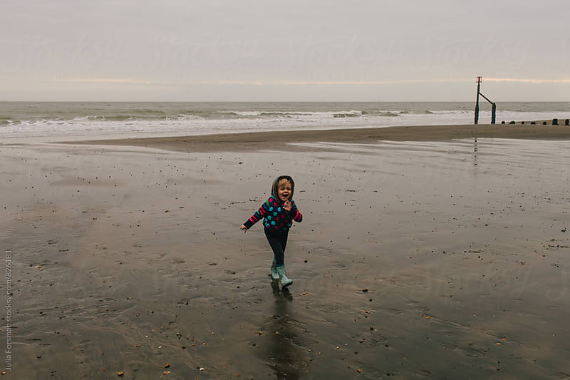 Little girl laughs as she walks towards the camera on beach with beautiful light in winter. by Julia Forsman for Stocksy United