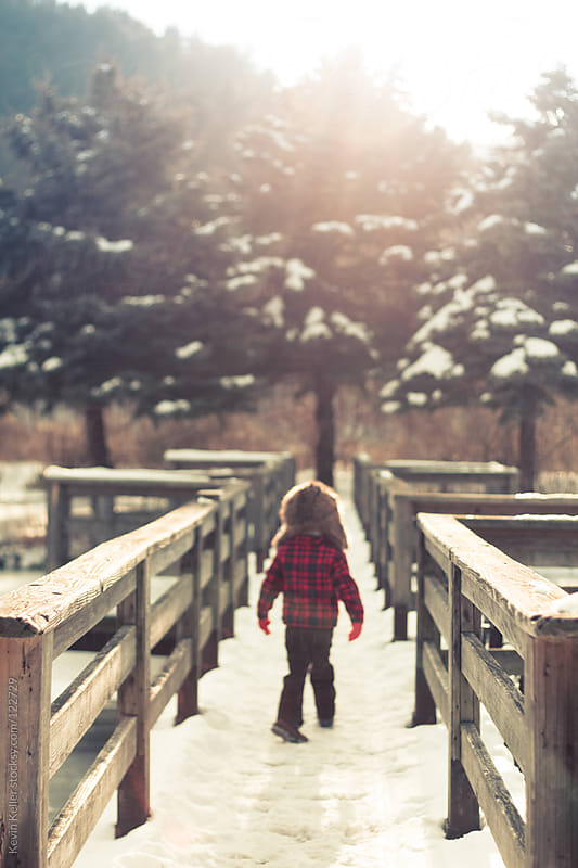 Young Boy Walking on a Snow Covered Bridge by Kevin Keller for Stocksy United