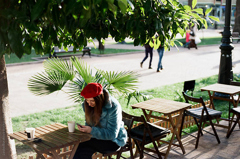 Young woman uses smartphone in outdoors cafe by Lyuba Burakova for Stocksy United