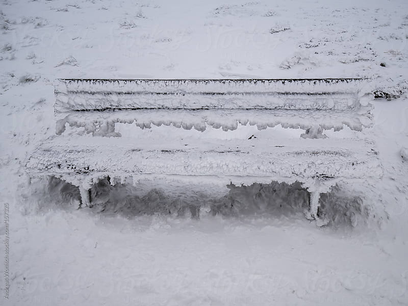 Snow covered, frozen bench by Andreas Wonisch for Stocksy United