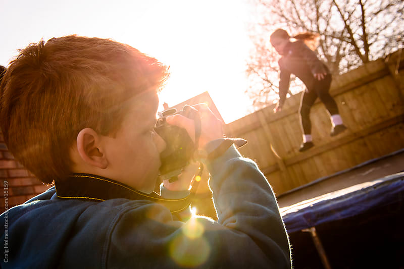 Boy photographing a girl jumping on a trampoline by Craig Holmes for Stocksy United