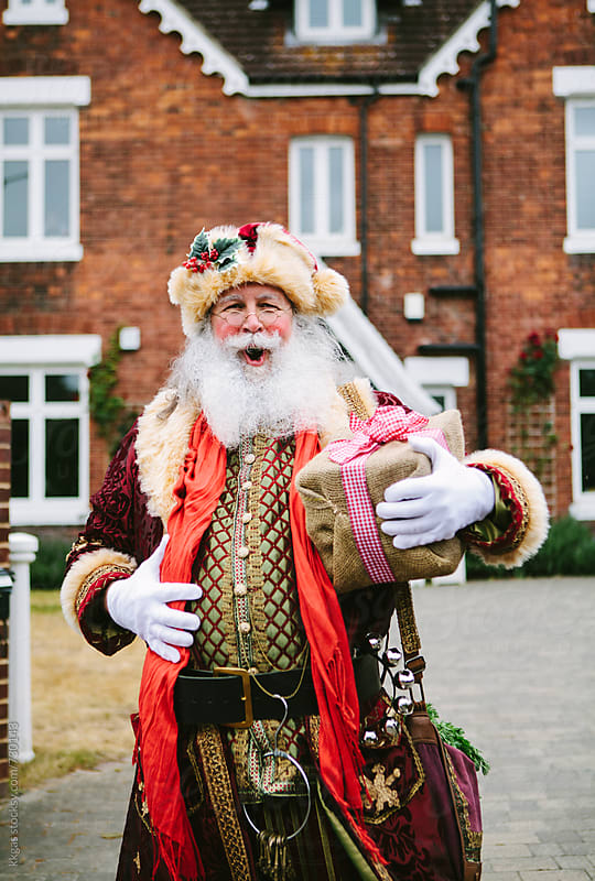 Santa Claus with a gift in front of a large house by kkgas for Stocksy United