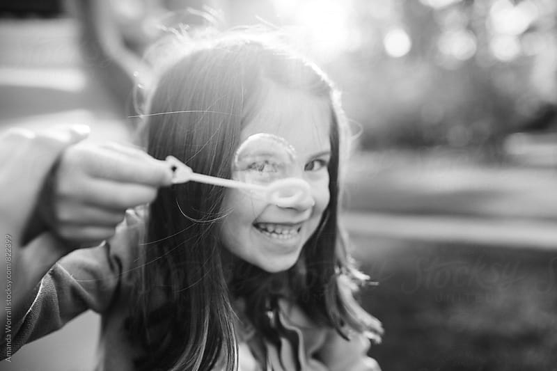 Smiling girl holding up bubble wand, looking though the bubble, monochrome by Amanda Worrall for Stocksy United
