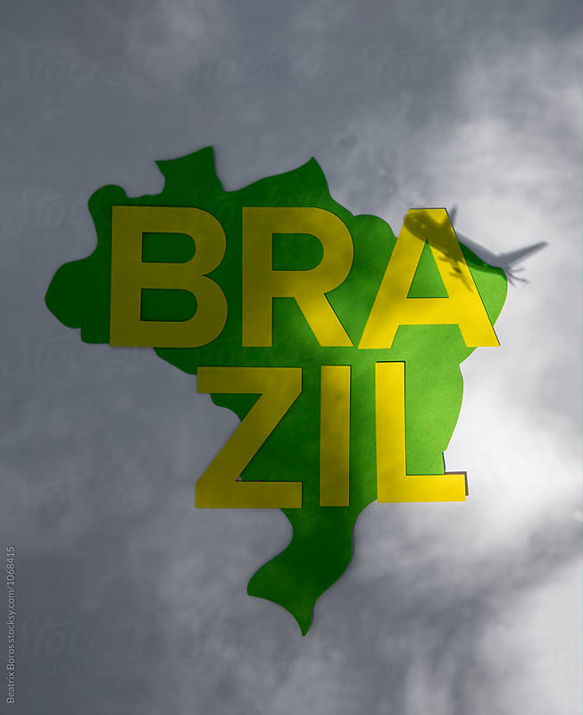 The shadow of an airplane flying over the shape of Brazil by Beatrix Boros for Stocksy United