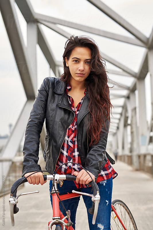 Young woman with her bicycle in a bridge by Guille Faingold for Stocksy United